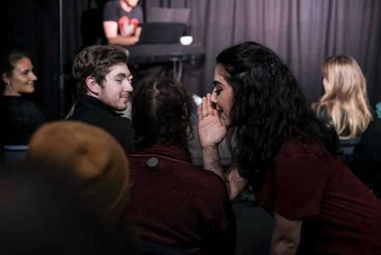 Woman whispering into an audience member's ear
